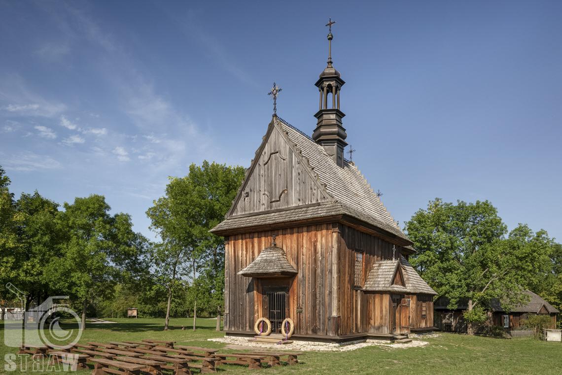 Fotografia architektury, zdjęcia budynków w skansenie wsi w Kielcach, drewniany kościółek, a przed nim ławki dla uczestników mszy św.