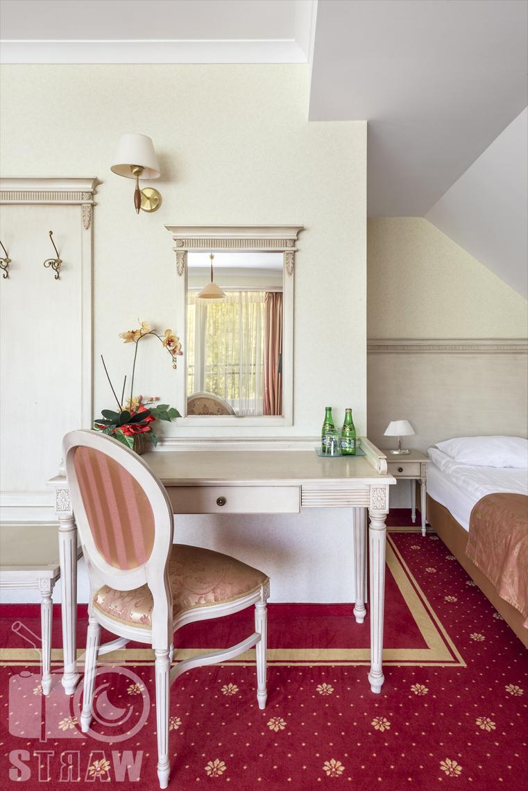 Zdjęcia wnętrz komercyjnych, hotel, apartament, toaletka z lustrem, krzesło, kwiaty, lampka wisząca.