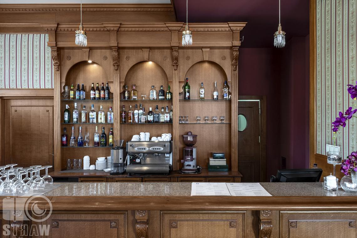 Zdjęcia wnętrz komercyjnych, hotel, bar hotelowy, kieliszki, w regale różne rodzaje butelek z alkoholami, express do kawy.