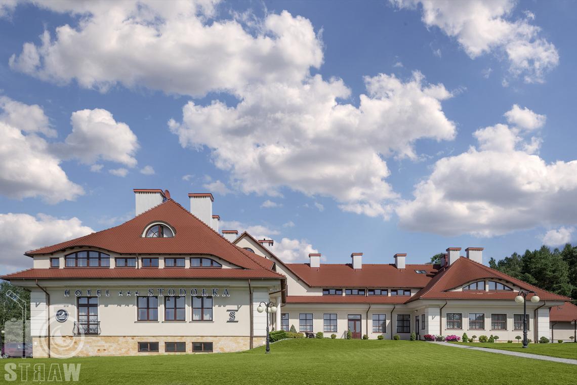 Zdjęcia wnętrz komercyjnych, hotel, widok budynku hotelowego z trawnikiem, lampami.