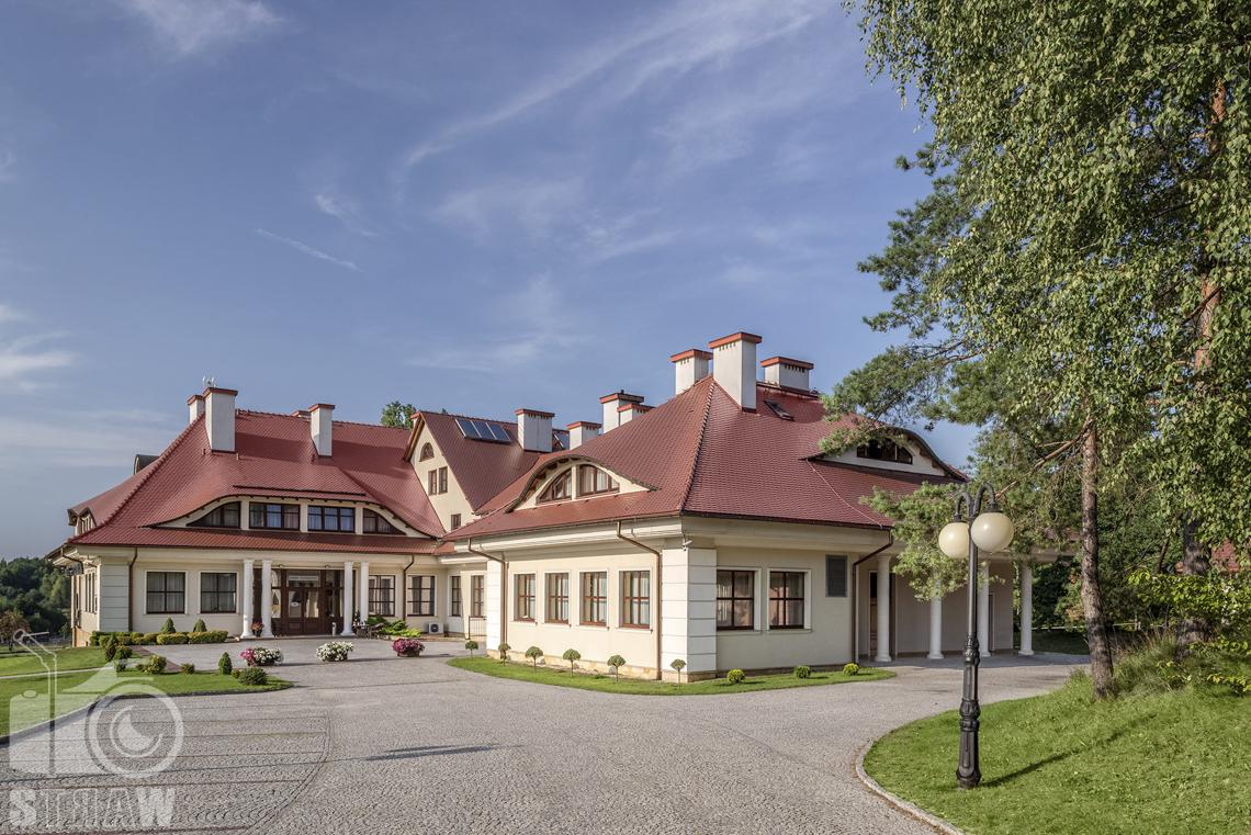 Zdjęcia wnętrz komercyjnych, hotel, Cały budynek hotelowy z podjazdem, widoczne kwiaty w donicach, lampa podwójna i dużo zieleni.