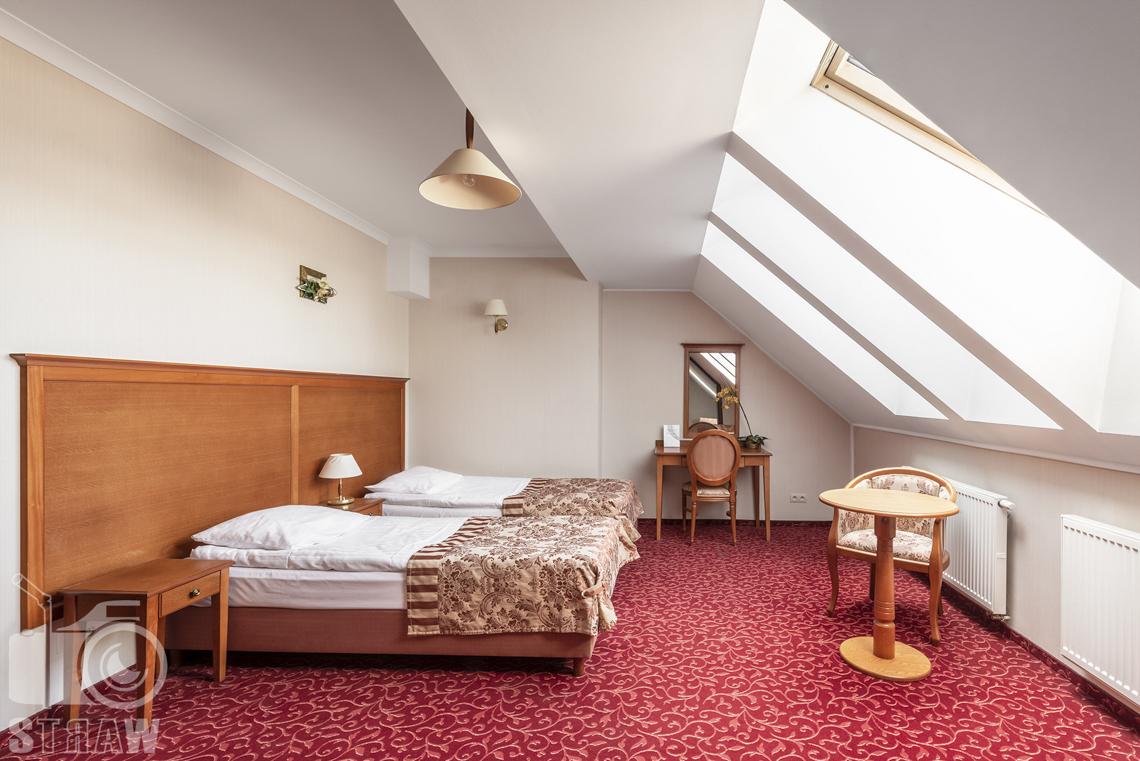 Zdjęcia wnętrz komercyjnych, hotel, pokój dwuosobowy na poddaszu, dwa łóżka, etażerka z lustrem, fotel, stół, dwie szafki nocne.