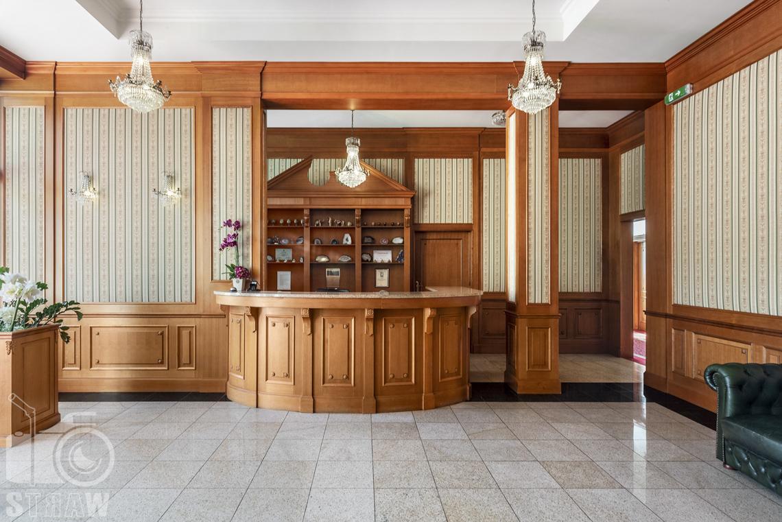 Zdjęcia wnętrz komercyjnych, hotel, recepcja hotelowa, pulpit recepcyjny i półki, trzy żyrandole.