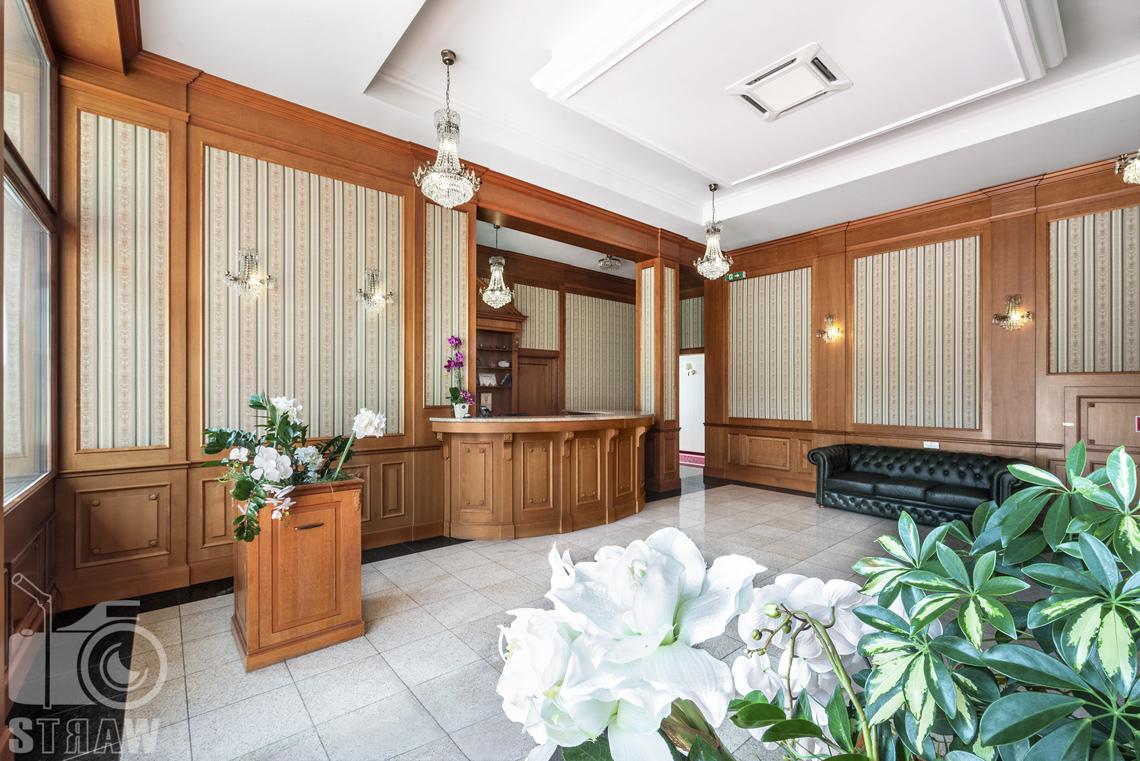 Zdjęcia wnętrz komercyjnych, hotel, recepcja hotelowa, dużo białych kwiatów, przy ścianie kanapa.