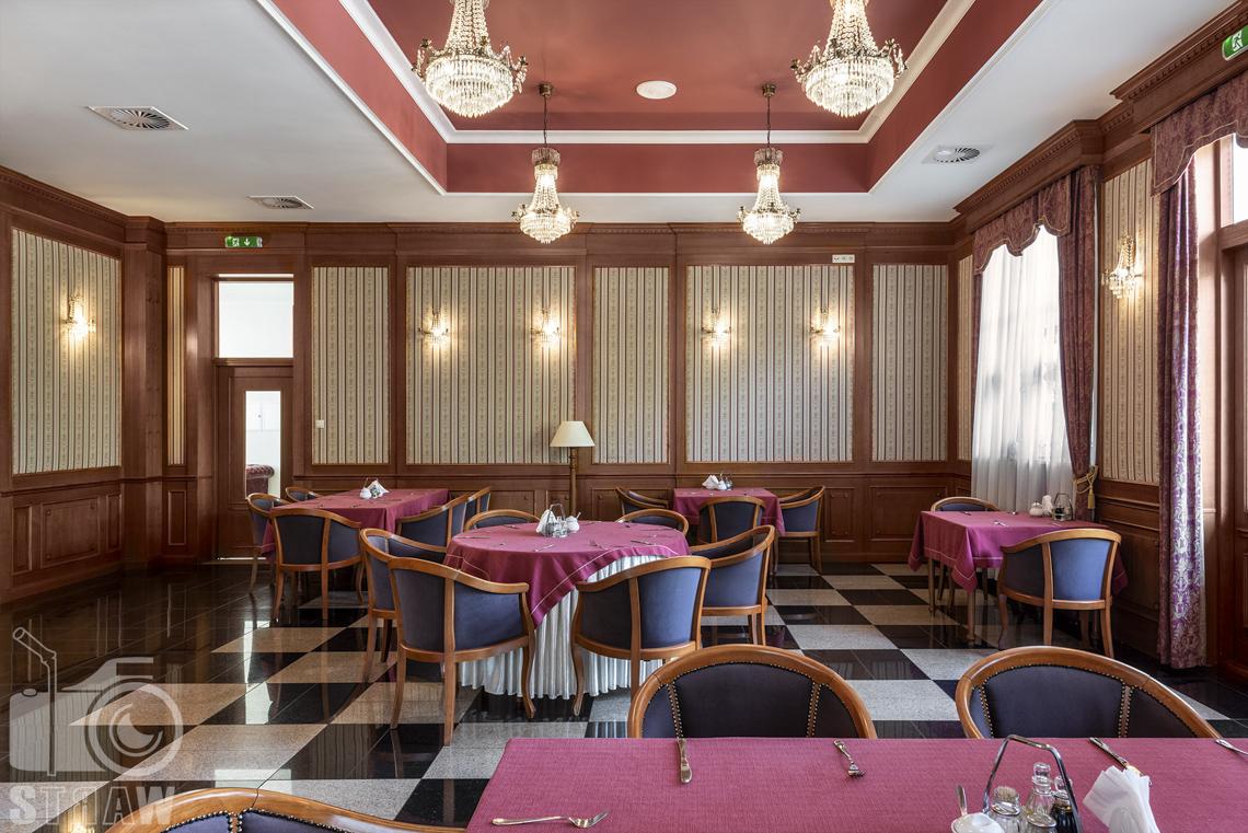 Zdjęcia wnętrz komercyjnych, hotel, Kawiarnia hotelowa, stoły okrągłe i prostokątne nakryte czerwonymi obrusami, wokół nich foteliki. Przy suficie cztery żyrandole.