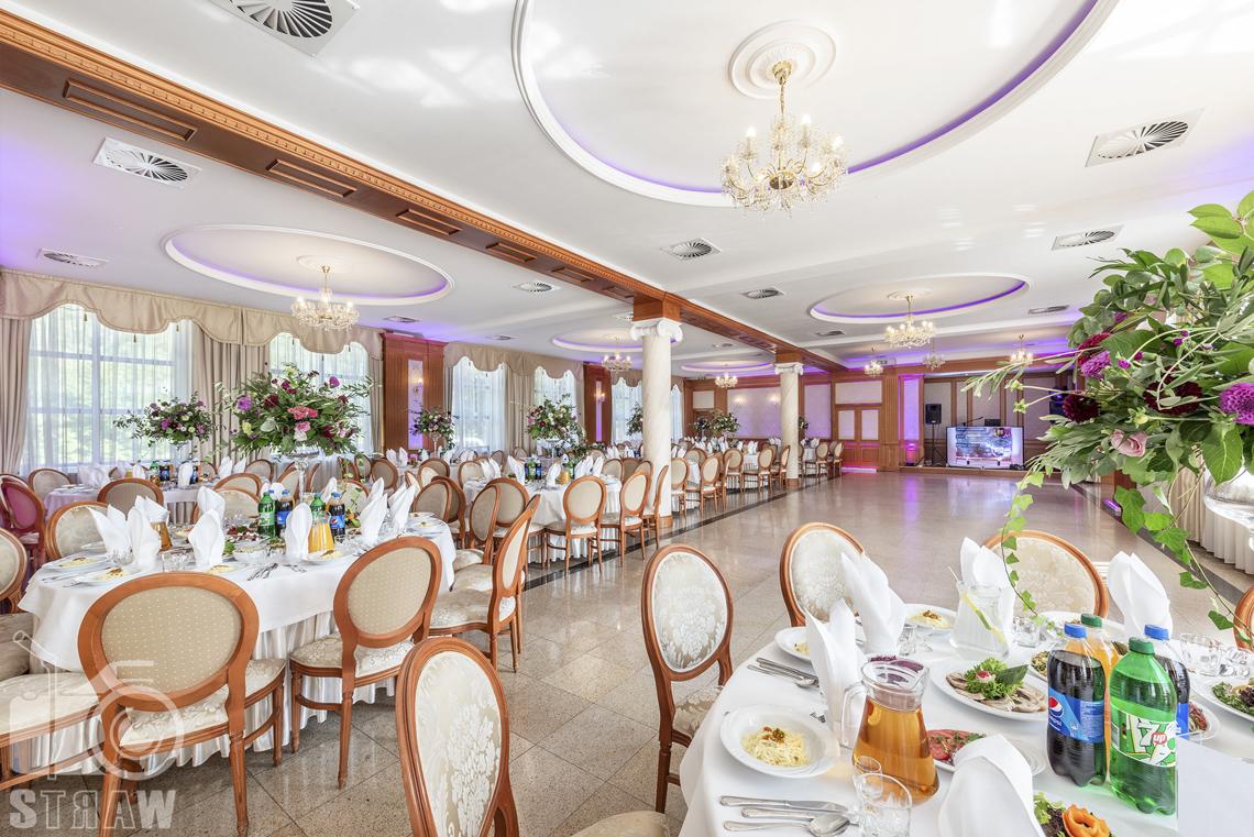 Zdjęcia wnętrz komercyjnych, hotel, sala jadalna i balowa, stoły nakryte białymi obrusami, na stołach napoje, serwetki, talerze i sztućce, kwiaty w dużych wazonach na podłodze..