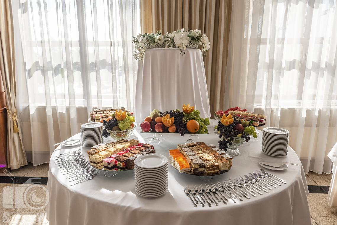 Zdjęcia wnętrz komercyjnych, hotel, stół z przygotowanymi weselnymi ciastami, owocami, talerzyki, sztućce.