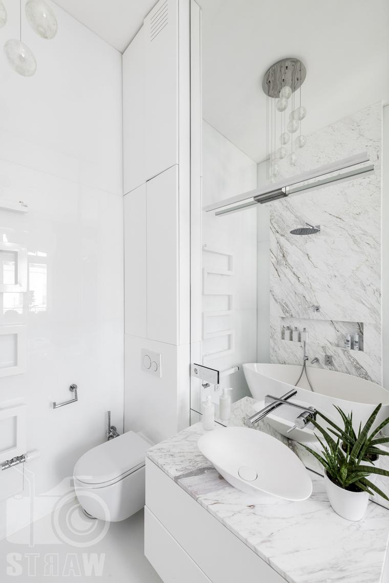 Zdjęcia mieszkania na sprzedaż w Warszawie, łazienka przy głównej sypialni marmur, umywalka i wc.