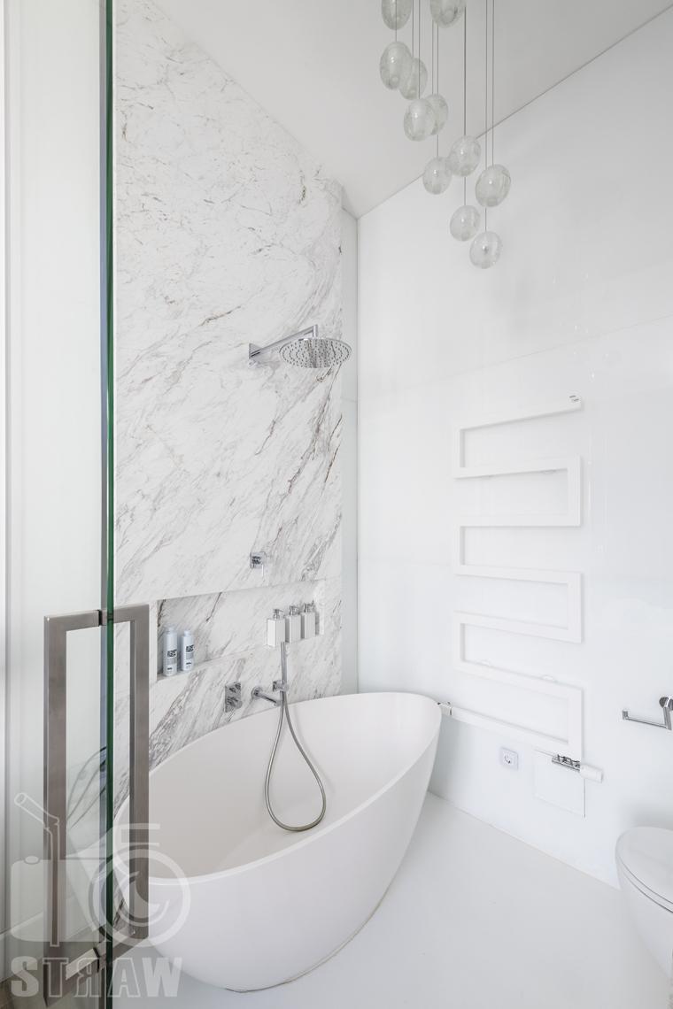 Zdjęcia mieszkania na sprzedaż w Warszawie, łazienka przeszklona ściany marmur, wanna i żyrandol.