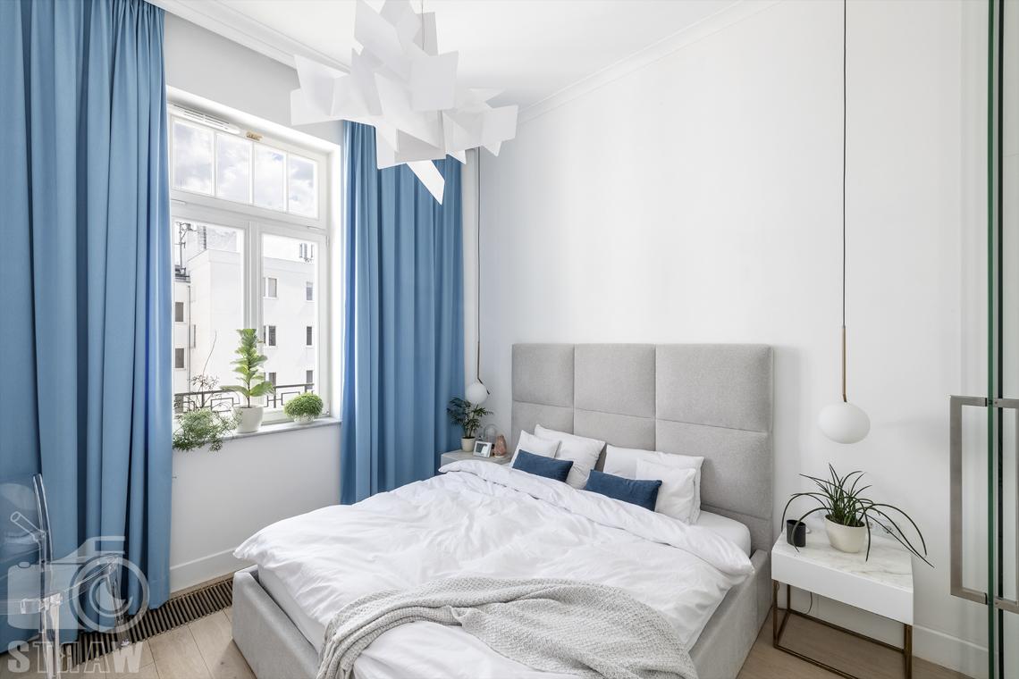 Zdjęcia mieszkania na sprzedaż w Warszawie, sypialnia z niebieskimi zasłonami, łózko z szarym zagłówkiem.