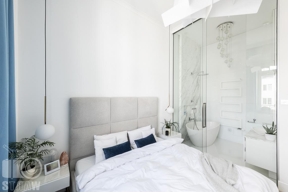 Zdjęcia mieszkania na sprzedaż w Warszawie, sypialnia z łóżkiem i przeszkloną łazienką.