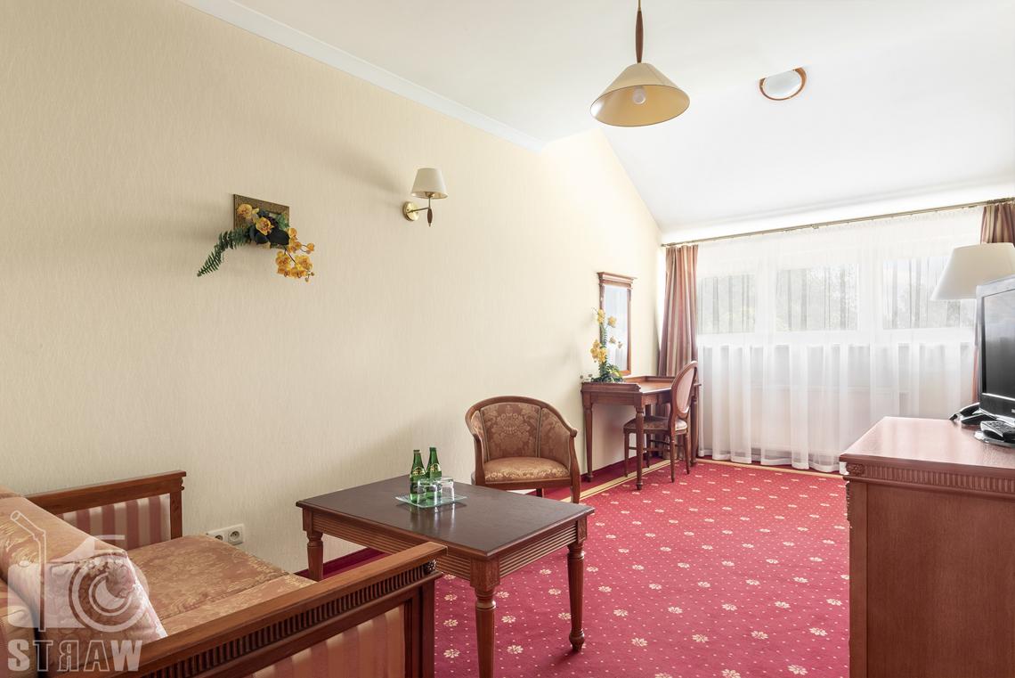 Zdjęcia wnętrz komercyjnych, hotel, apartament, pokój wypoczynkowy, dwa fotele, stolik z wodą mineralna i szklankami. Dalej toaletka z krzesłem.