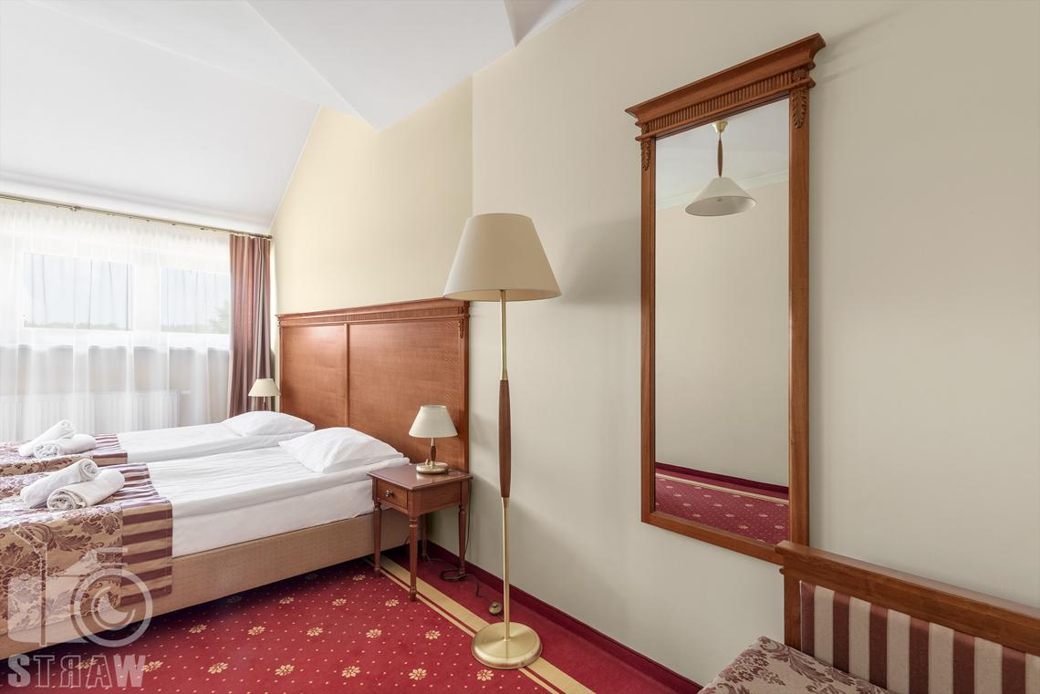 Zdjęcia wnętrz komercyjnych, hotel, apartament, sypialnia, łóżko dwuosobowe, dwie szafki nocne z lampkami, lampa stojąca, duze lustro.