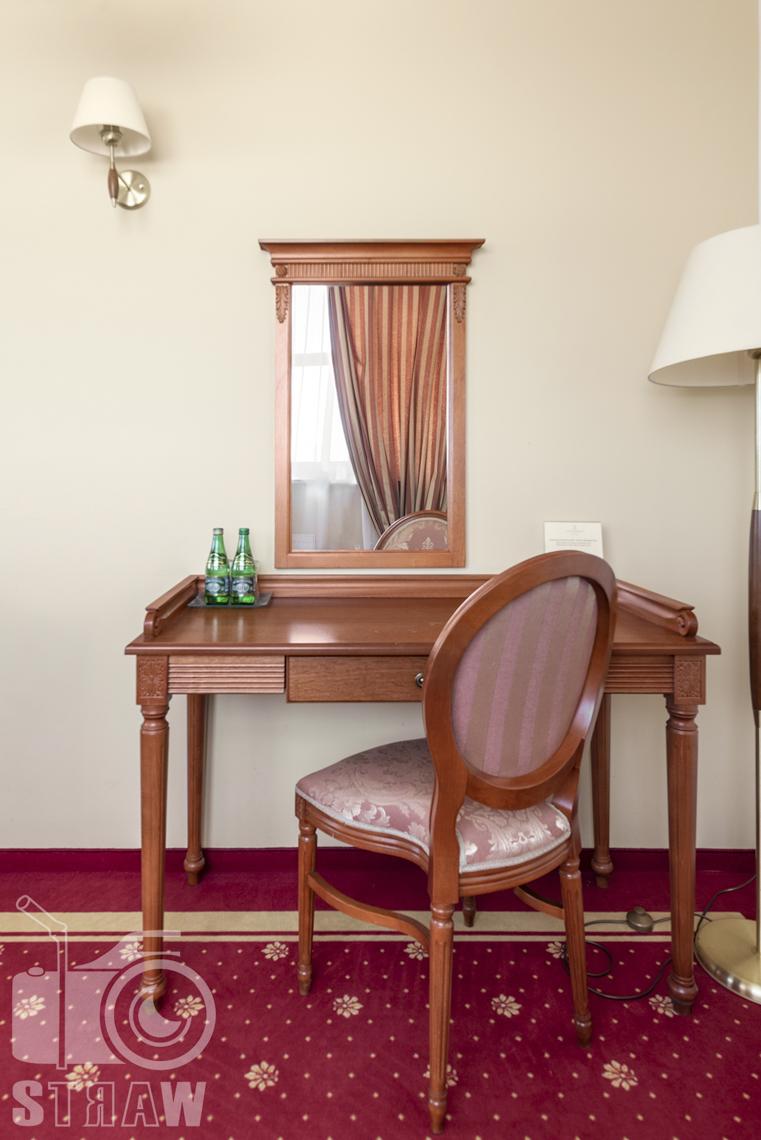 Zdjęcia wnętrz komercyjnych, hotel, toaleta z lustrem obok krzesło wyściełane.