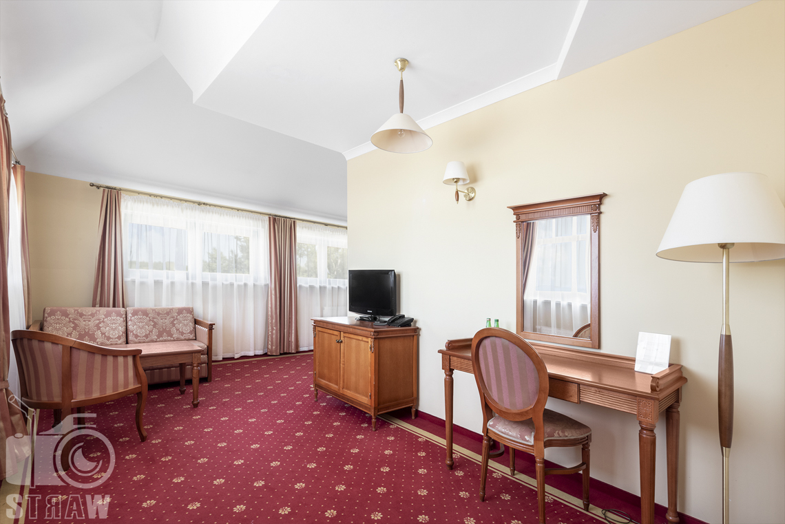 Zdjęcia wnętrz komercyjnych, hotel, apartament, toaletka z lustrem, lampa stojąca, dalej stół, kanapa, fotel na tle okien.
