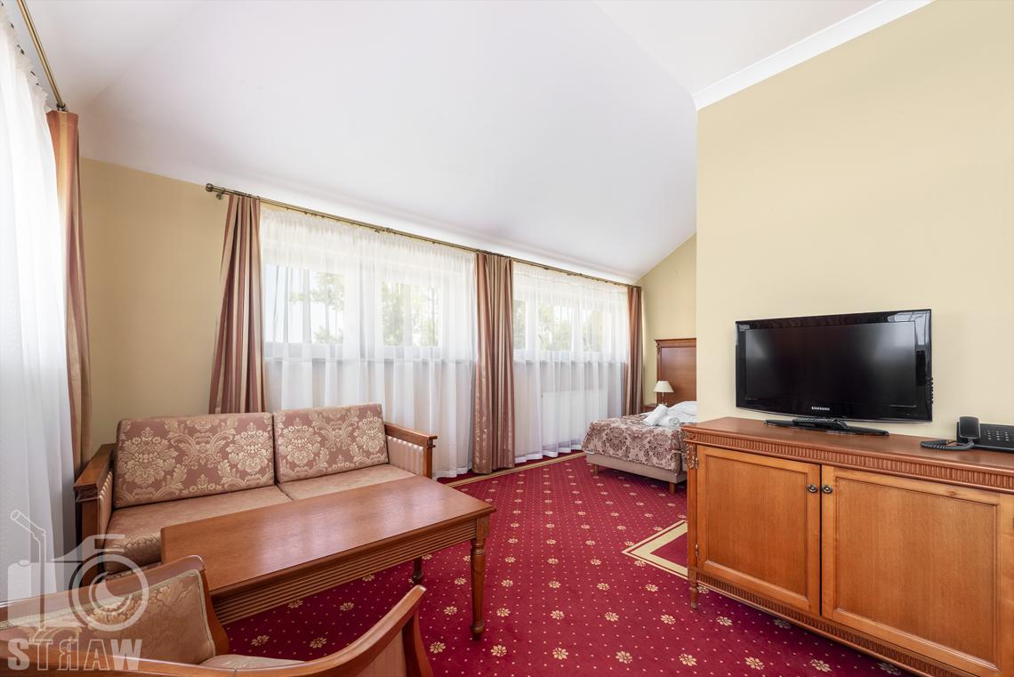 Zdjęcia wnętrz komercyjnych, hotel, apartament, część wypoczynkowa, stół, kanapa, fotel, szafka z telewizorem.