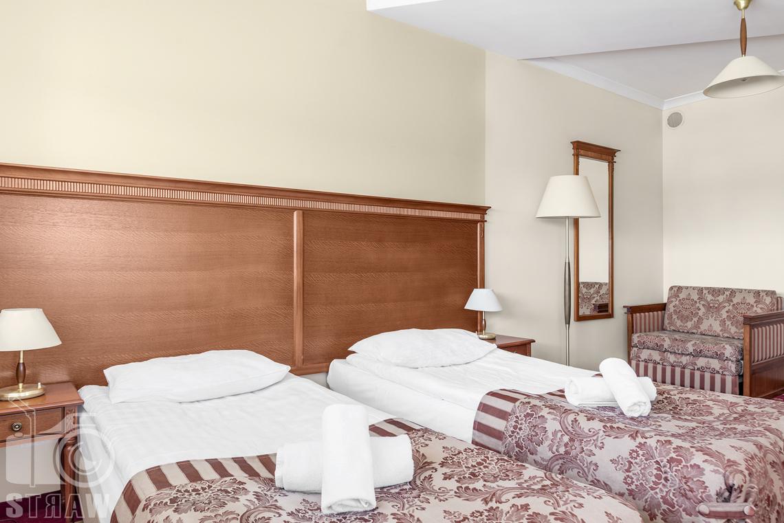 Zdjęcia wnętrz komercyjnych, hotel, apartament, dwa łóżka, fotel, lustro, szafki nocne z lampkami, lampa stojąca i lampa wisząca.