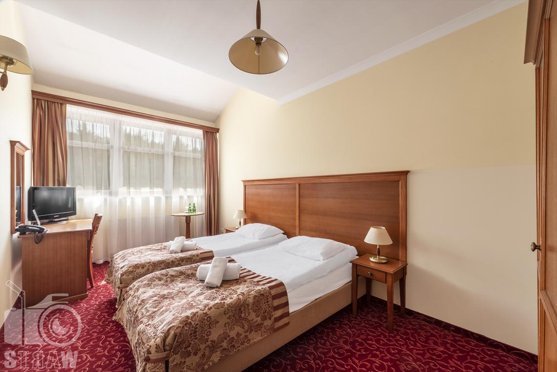 Fotografia nieruchomości komercyjnych, hoteli, restauracji, pokój hotelowy, dwa łóżka, telewizor, dwie lampki nocne na szafkach, duże okno.