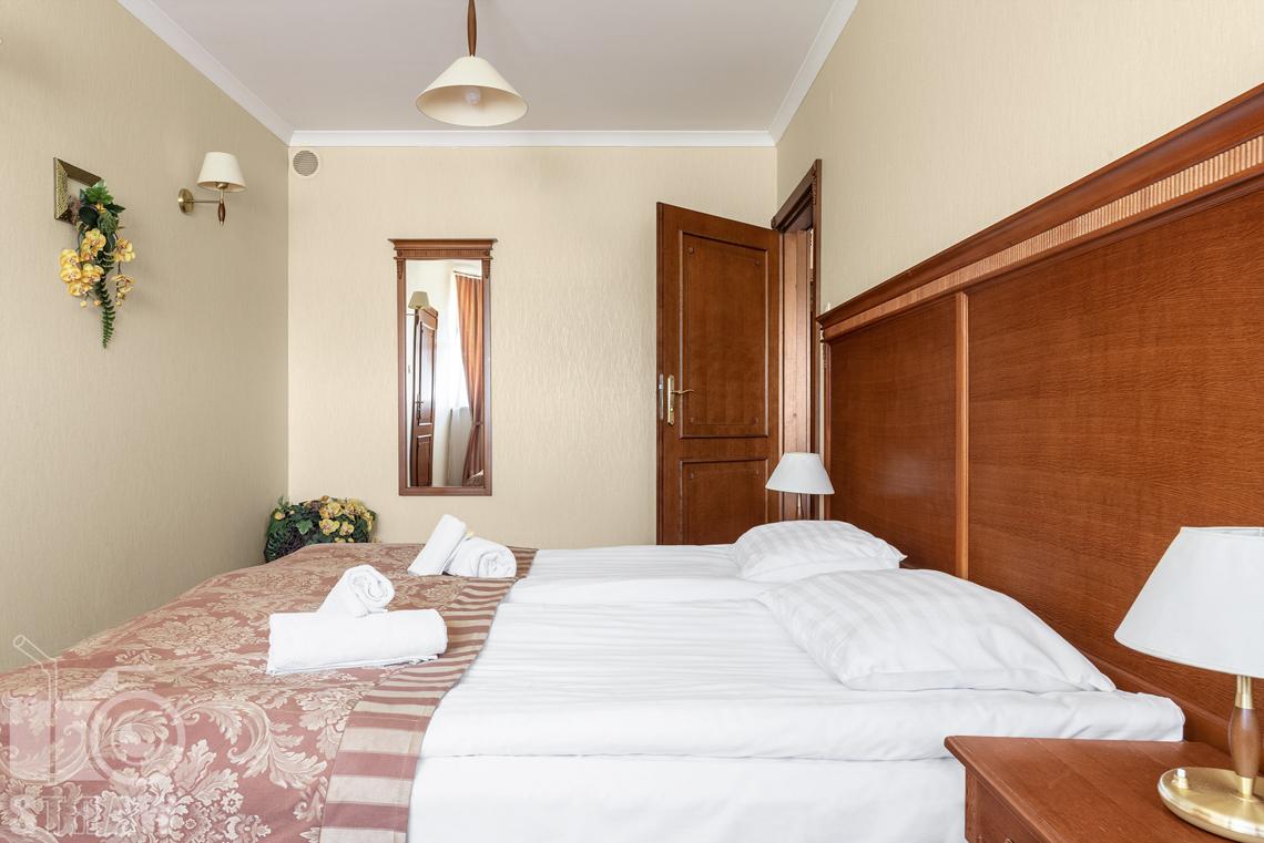 Zdjęcia wnętrz komercyjnych, hotel, pokój dwuosobowy łóżko podwójne, kwiaty w rogu pokoju, lustro wiszące, dwie szafki nocne z lampkami.
