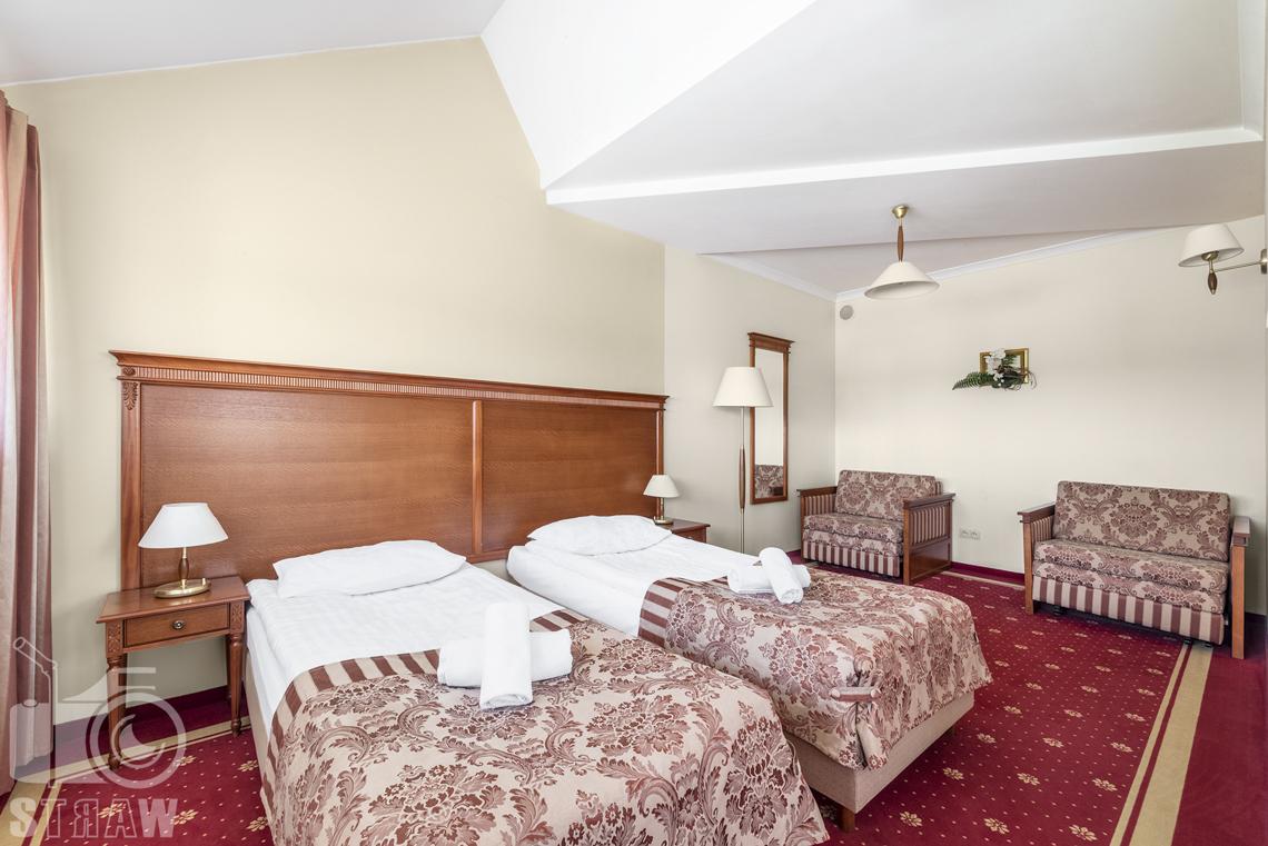 Zdjęcia wnętrz komercyjnych, hotel, apartament sypialnia, dwa łóżka, fotel i kanapa, dwie szafki nocne z lampkami, lustro, lampa stojąca i wisząca.