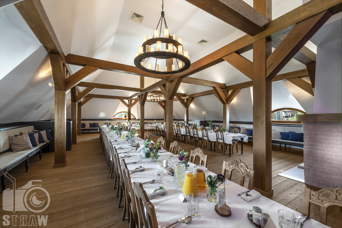 Zdjęcia karczmy Kuźnia smaków, Kielce, restauracji, sali weselnej, sala jadalna kominkowa, stoły ustawione wzdłuż, obok siebie, wokół sali przy ścianach kanapy z poduchami.