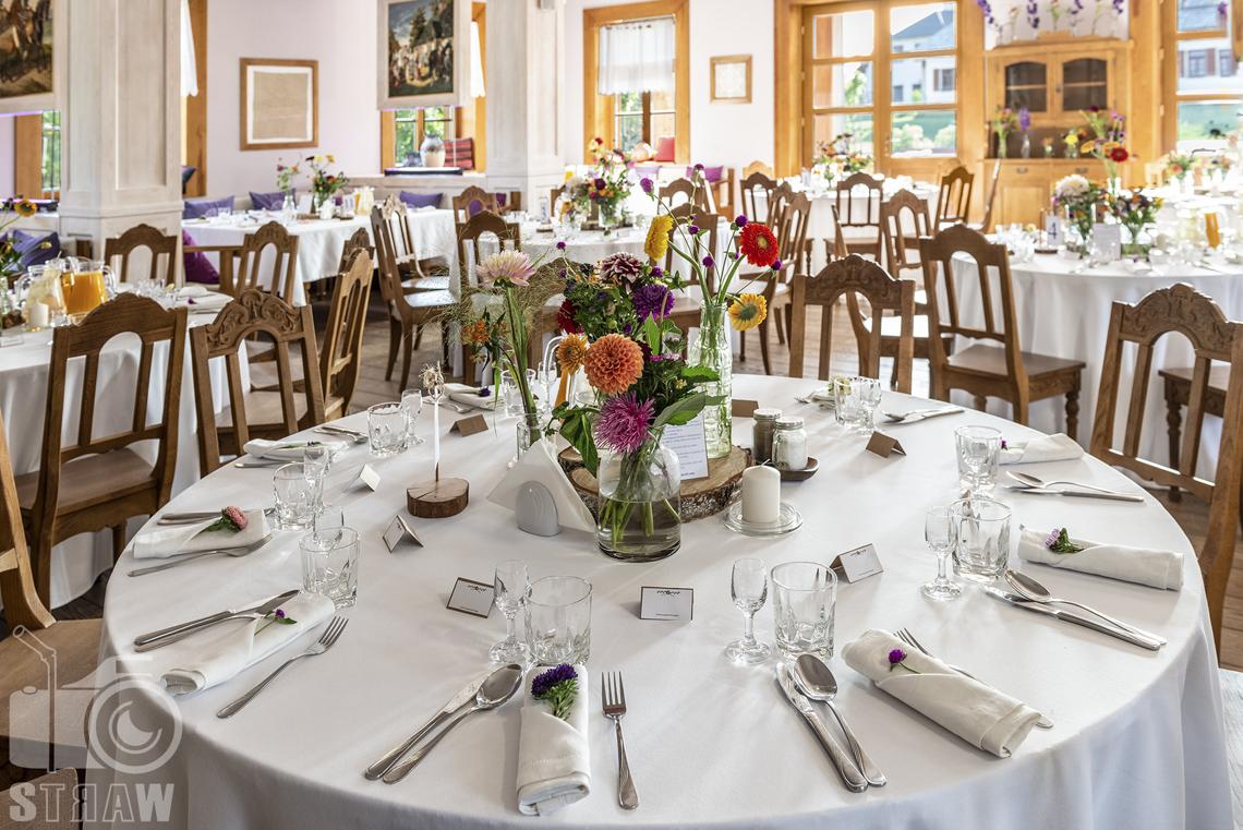 Zdjęcia karczmy Kuźnia smaków, Kielce, restauracji, sali weselnej, w sali jadalnej okrągły stół nakryty białym obrusem, położone sztuśce, stoja kieliszki i szklanki do napojów, kwiaty w wazonach.