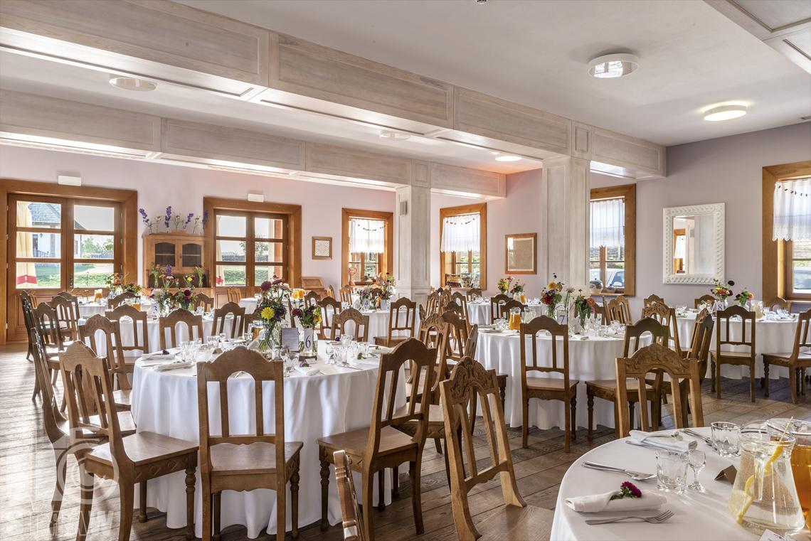Zdjęcia karczmy Kuźnia smaków, Kielce, restauracji, sali weselnej, sala jadalna z wieloma okrągłymi stołami, wokół nich krzesła, na ścianach wiele okien.