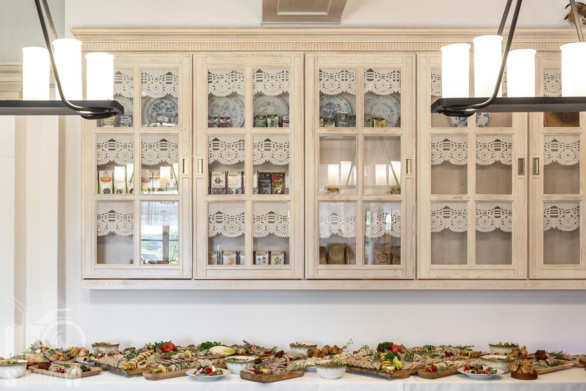 Zdjęcia karczmy Kuźnia smaków, Kielce, restauracji, sali weselnej, stół z potrawami weselnymi, szafka stylizowana jasna.