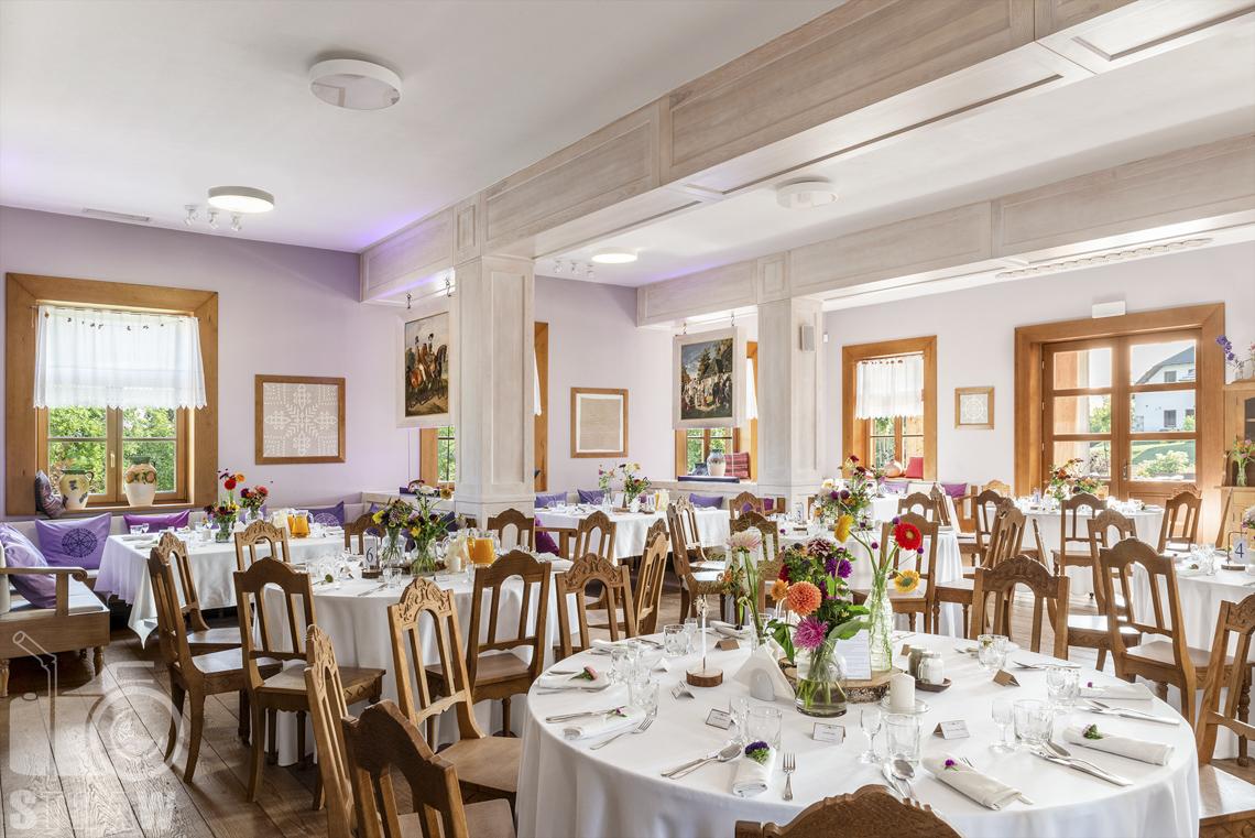 Zdjęcia karczmy Kuźnia smaków, Kielce, restauracji, sali weselnej, sala jadalna z okrągłymi stołami nakrytymi białymi obrusami, kwiaty w wazonach, wokół stołów krzesła.