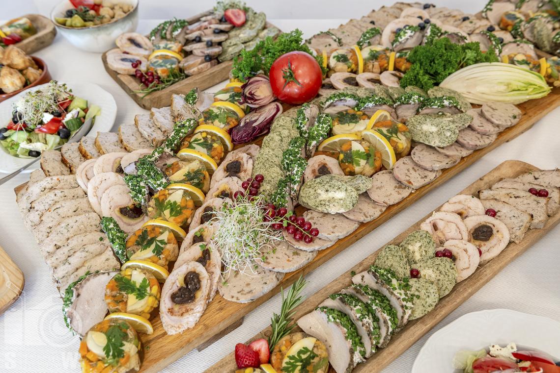 Zdjęcia karczmy Kuźnia smaków, Kielce, restauracji, sali weselnej, Na półmiskach drewnianych różne rodzaje wędlin.