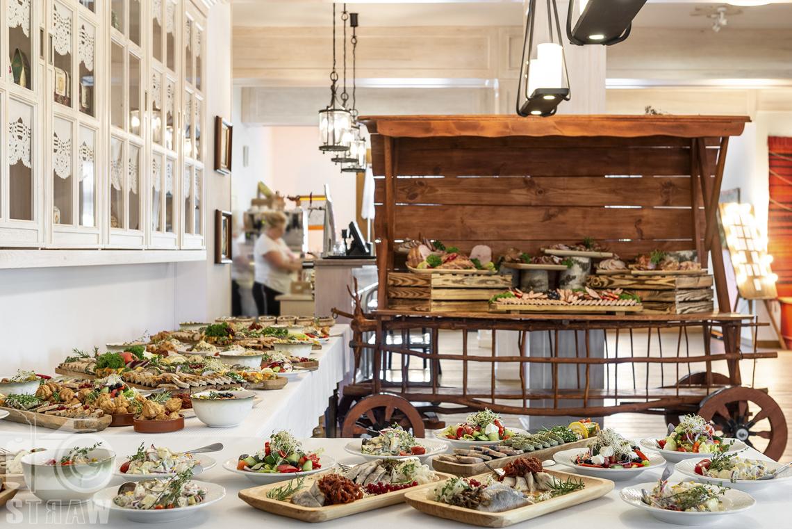 Zdjęcia karczmy Kuźnia smaków, Kielce, restauracji, sali weselnej, Na stołach i w stylizowanym wozie półmiski z potrawami na wesele, na ścianie szafka.