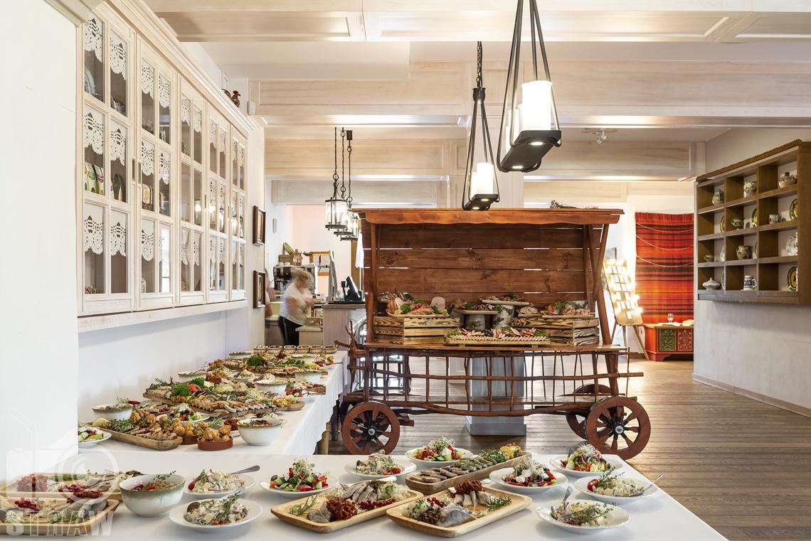 Zdjęcia karczmy - Kuźnia smaków, restauracji, sali weselnej, Na stołach i w stylizowanym wozie półmiski z potrawami na wesele, na ścianach szafki.