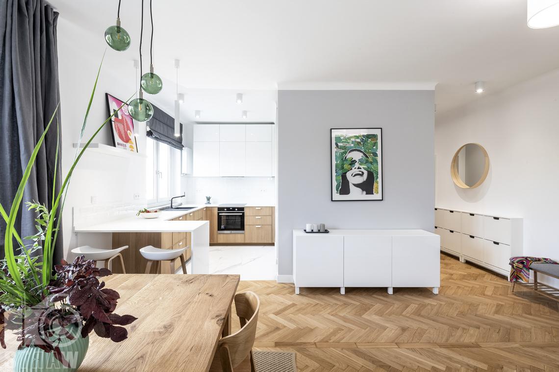 Sesja fotograficzna nieruchomości na wynajem, jadalnia, salon, kuchnia i obraz na ścianie.