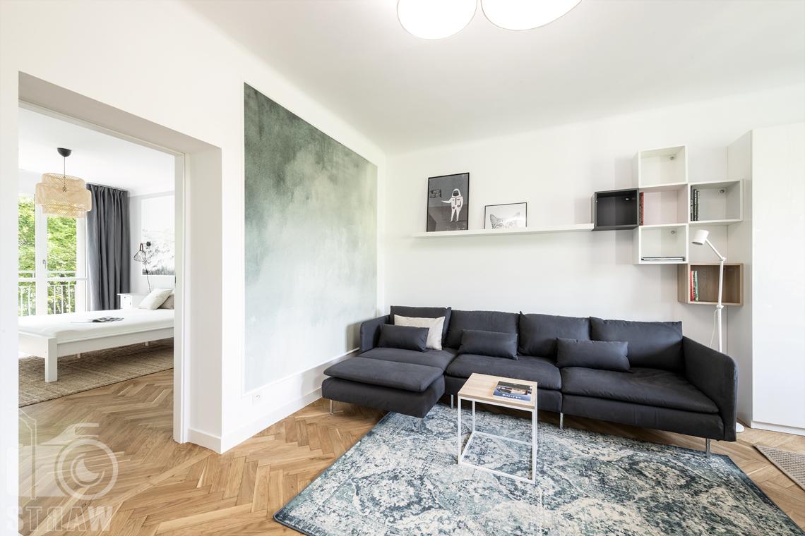 Sesja fotograficzna nieruchomości na wynajem, salon z sofą i stolikiem kawowym, otwarte drzwi do sypialni.