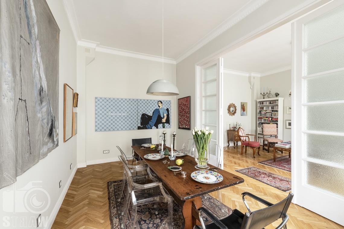 Zdjęcia mieszkania na sprzedaż zlokalizowanego w kamienicy na warszawskim Mokotowie, jadalnia, obrazy, stół i zastawa.