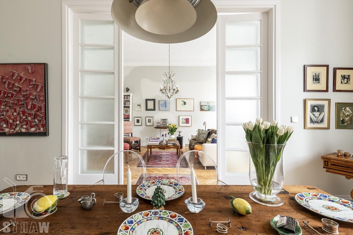 Zdjęcia mieszkania na sprzedaż zlokalizowanego w kamienicy na warszawskim Mokotowie, stół w jadalni, widok na salon.