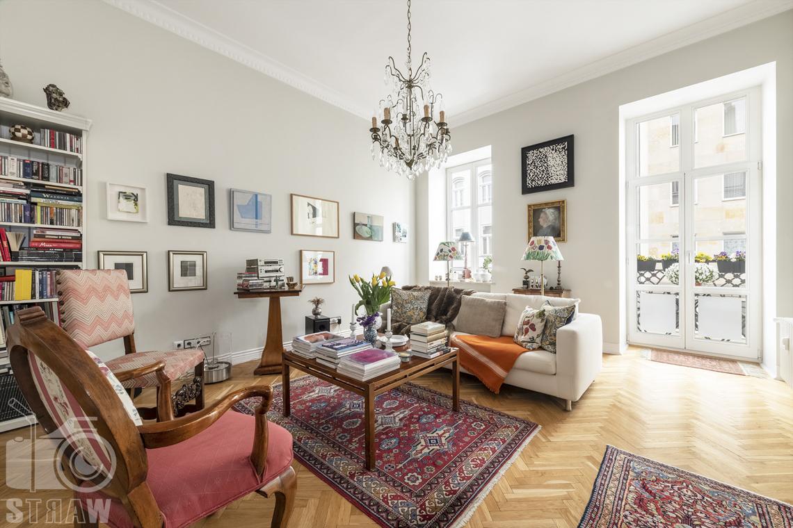 Zdjęcia mieszkania na sprzedaż zlokalizowanego w kamienicy na warszawskim Mokotowie, salon, fotele i sofa, stół i balkon.