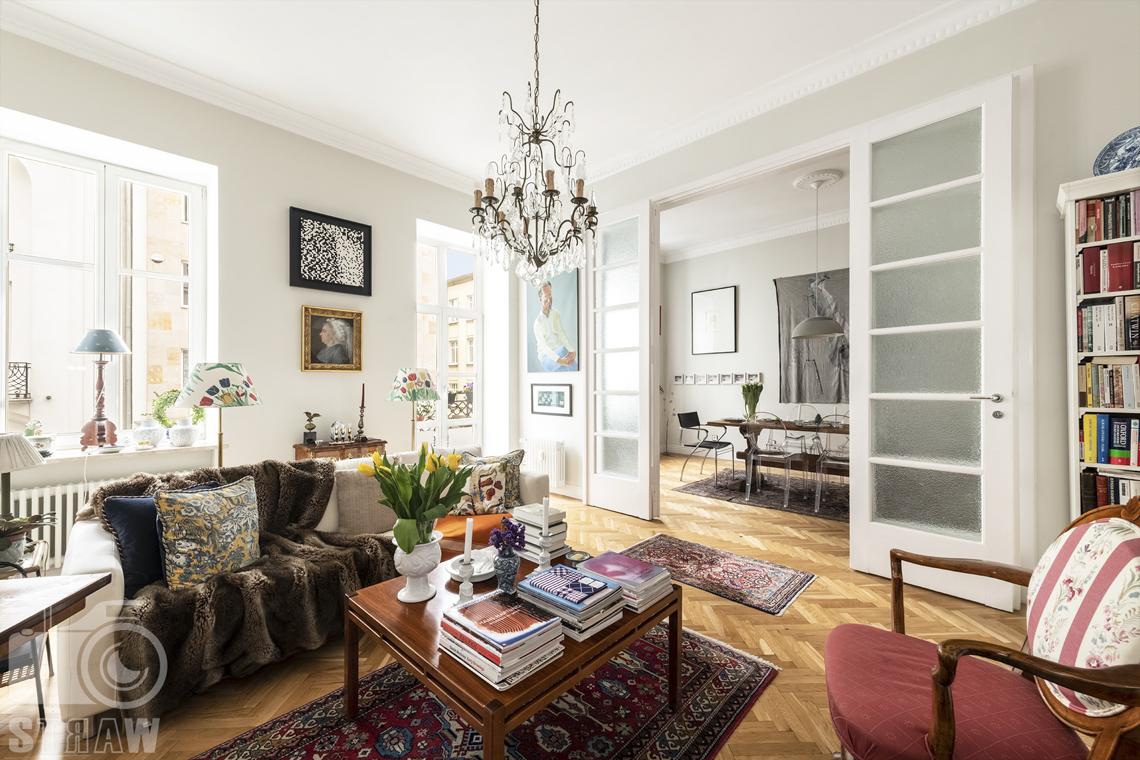 Zdjęcia mieszkania na sprzedaż zlokalizowanego w kamienicy na warszawskim Mokotowie, salon, stolik kawowy z książkami, widok na jadalnię.