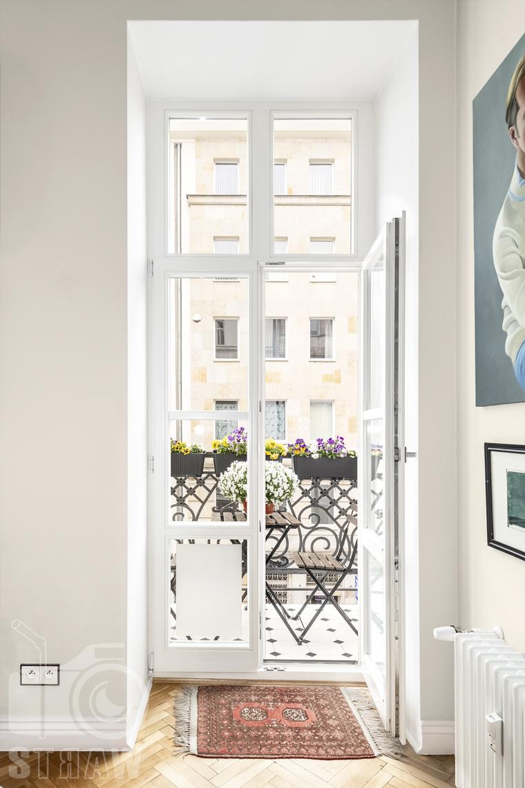 Zdjęcia mieszkania na sprzedaż zlokalizowanego w kamienicy na warszawskim Mokotowie, balkon z kwiatami i stolikiem, widok przez otwarte drzwi.
