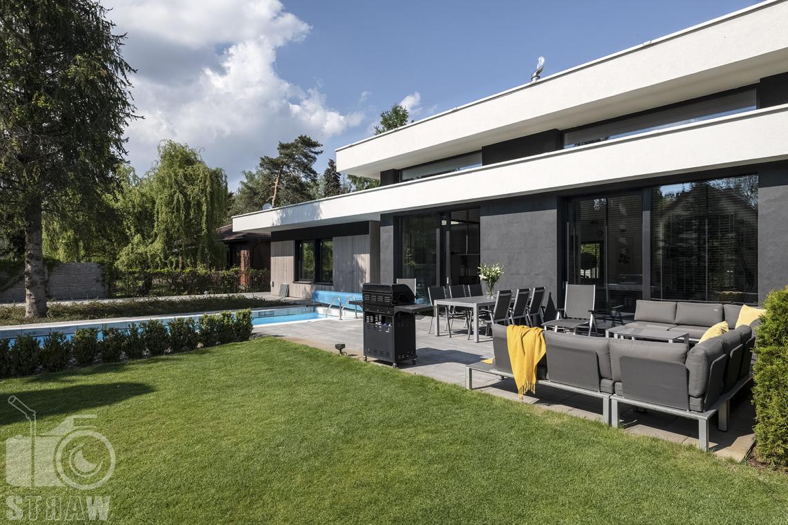 Zdjęcia nieruchomości na sprzedaż, dom w Komorowie, wypoczynek z sofami stołem, grillem i basenem w ogrodzie.