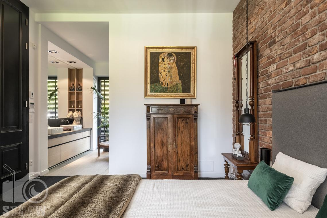 Zdjęcia nieruchomości na sprzedaż, dom w Komorowie, sypialnia, łózko, drewniana komoda, widok na otwartą łazienkę.