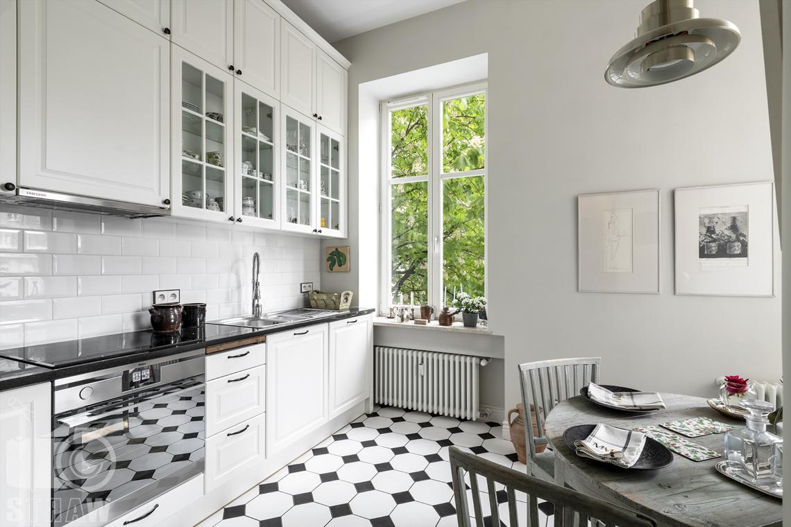 Zdjęcia mieszkania na sprzedaż zlokalizowanego w kamienicy na warszawskim Mokotowie, kuchnia z mozaiką, kuchenka i stół.