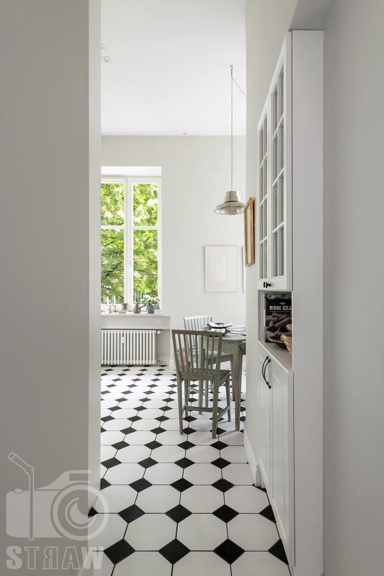 Zdjęcia mieszkania na sprzedaż zlokalizowanego w kamienicy na warszawskim Mokotowie, wejście do kuchni, podłoga z biało czarnej mozaiki, zieleń za oknem.