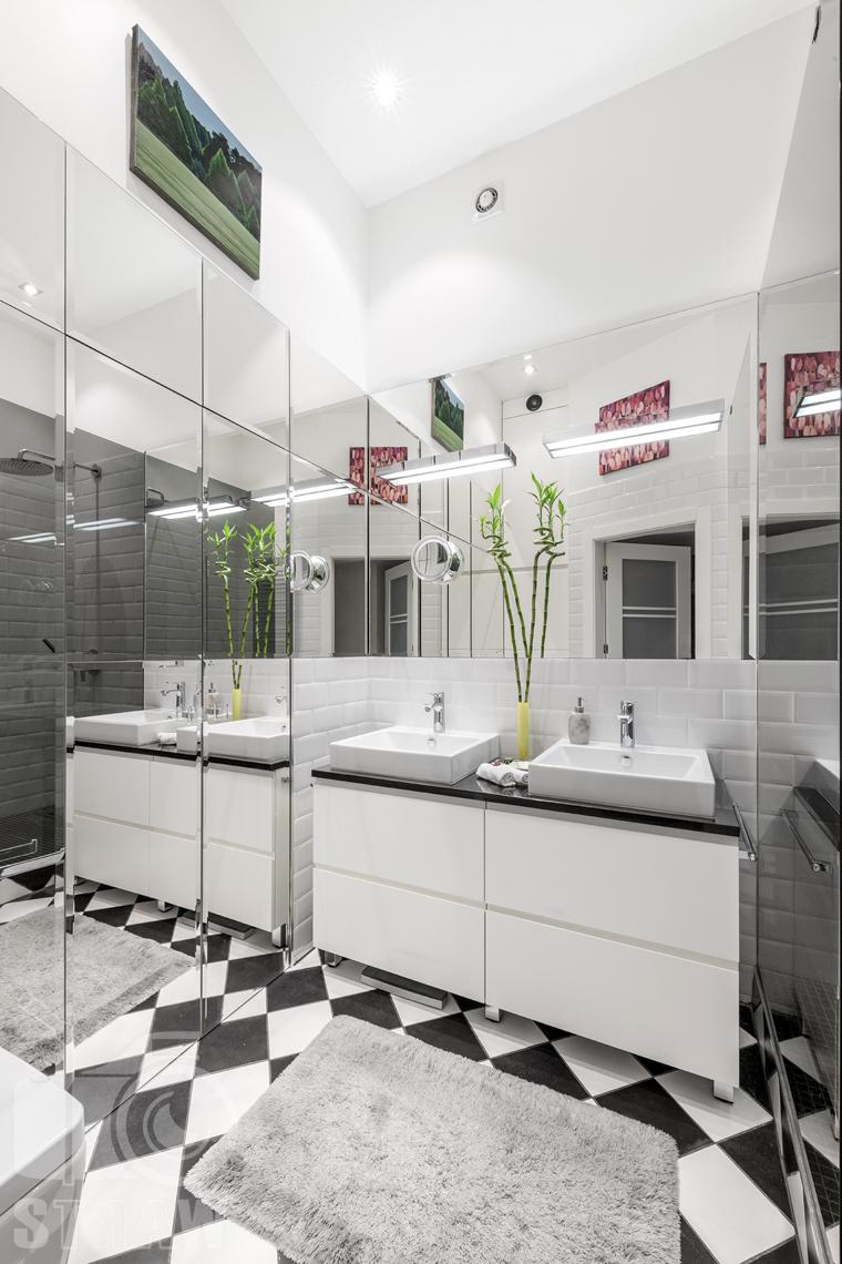 Zdjęcia mieszkania na sprzedaż zlokalizowanego w kamienicy na warszawskim Mokotowie, łazienka z umywalkami i lustrzaną szafą oraz z prysznicem.
