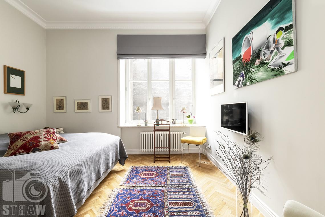 Zdjęcia mieszkania na sprzedaż zlokalizowanego w kamienicy na warszawskim Mokotowie, sypialnia, dywany, łóżko.