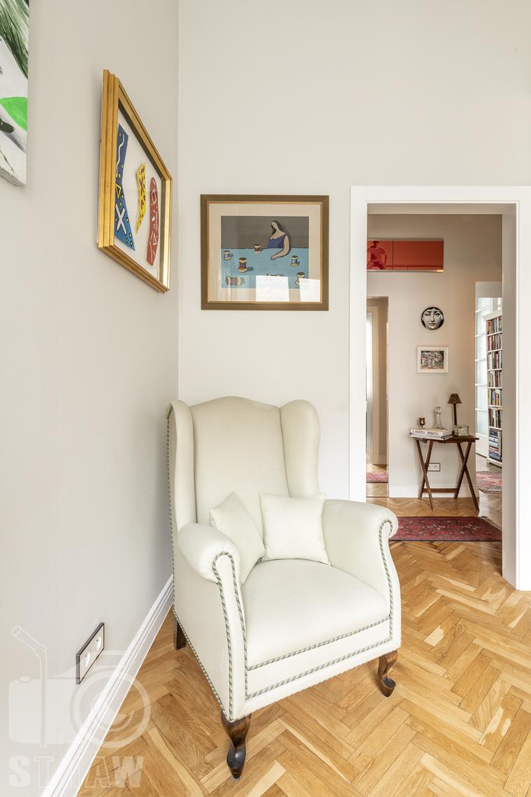 Zdjęcia mieszkania na sprzedaż zlokalizowanego w kamienicy na warszawskim Mokotowie, sypialnia, fotel, przedpokój.