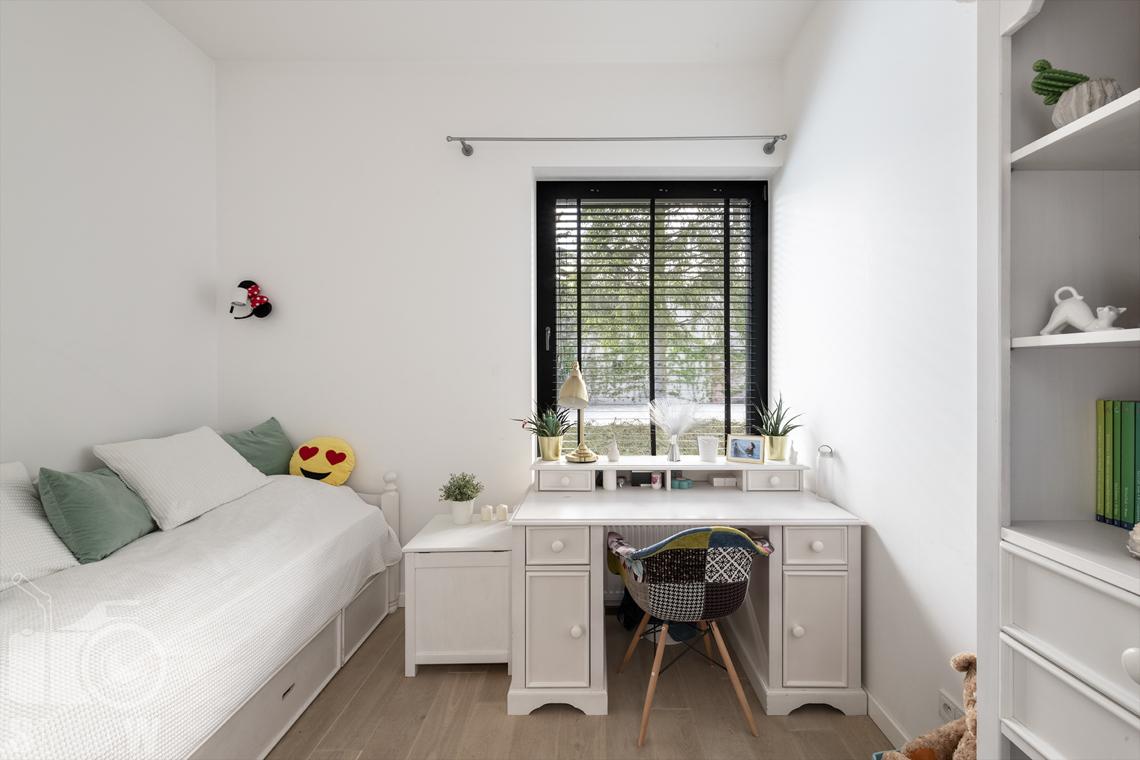 Zdjęcia nieruchomości na sprzedaż, dom w Komorowie, pokój dziewczynki z białym biurkiem.