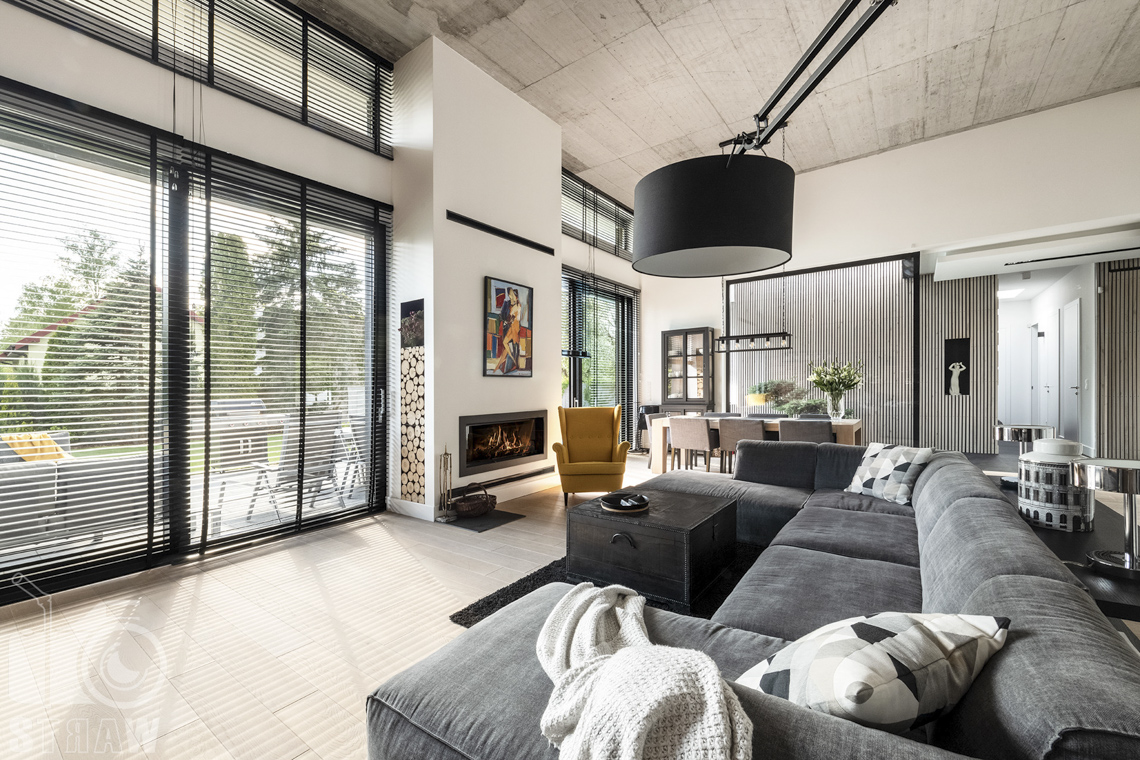 Zdjęcia nieruchomości na sprzedaż, dom w Komorowie, salon z szarą sofą i duże okna na całej ścianie budynku, kominek.