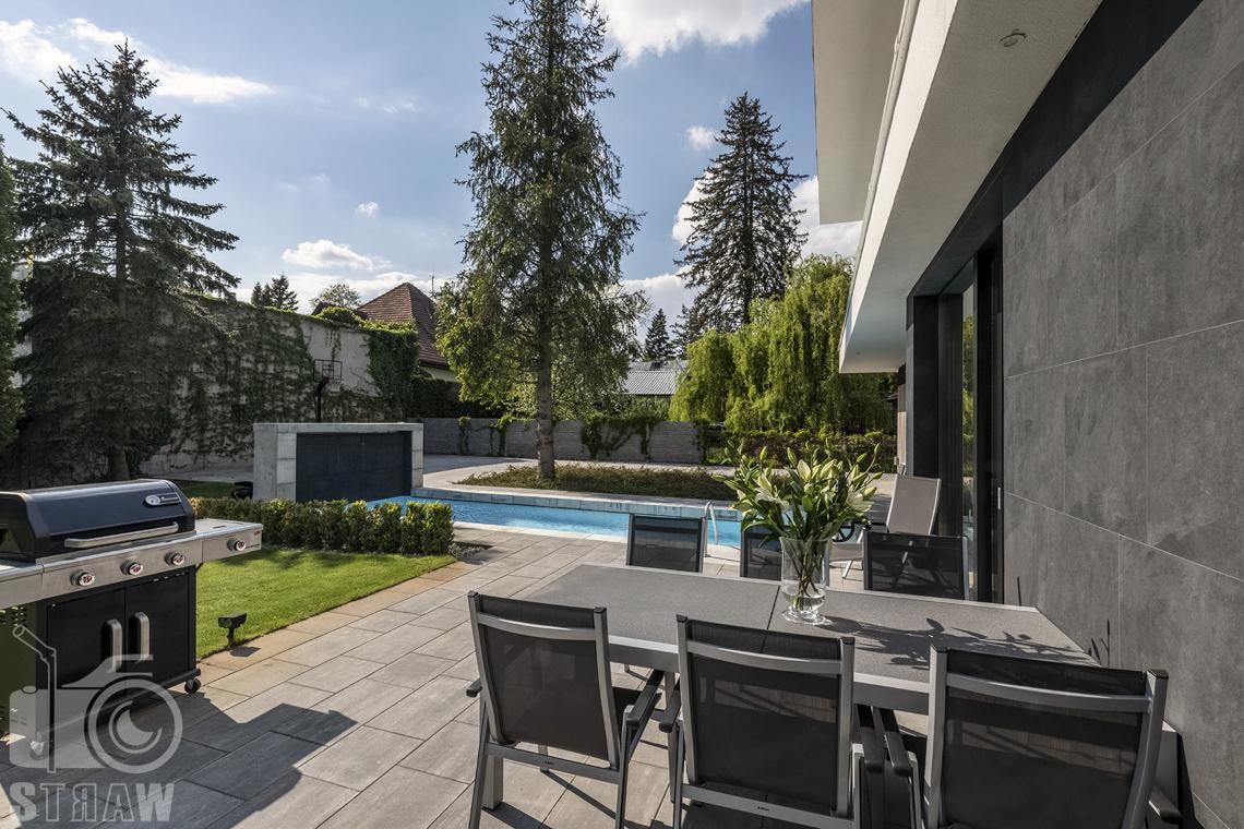 Zdjęcia nieruchomości na sprzedaż, dom w Komorowie, ogród z basenem, stół i zamykany gril.