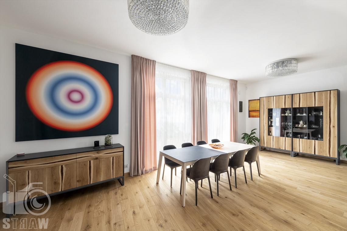 Zdjęcia domu na sprzedaż w lokalizacji Warszawa Wilanów, salon z dwukolorowym stołem, tęczowy obraz na ścianie i szafa.